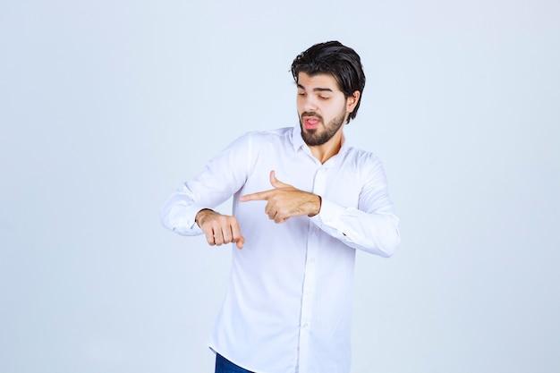 Man in een wit overhemd controleert zijn tijd