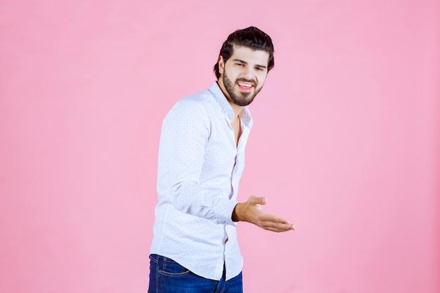 Man in een wit overhemd die de hand geeft om te schudden.