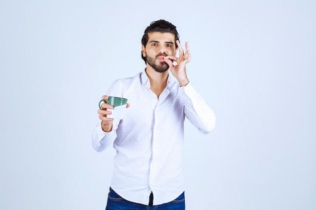 Man in een wit overhemd die een koffiemok vasthoudt en ervan geniet.