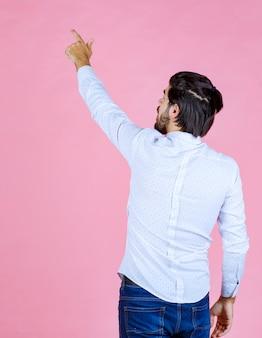 Man in een wit overhemd die zijn hand opsteekt om aandacht te krijgen of iets te laten zien.