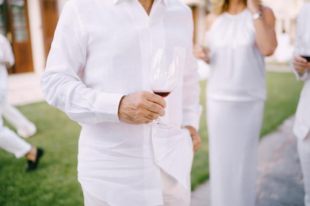 Man in een wit overhemd en broek staat met een glas rode wijn in zijn hand