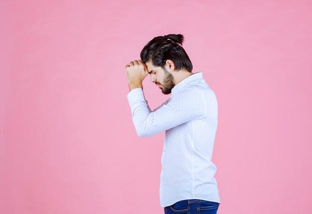 Man in een wit overhemd handen verenigen en bidden.