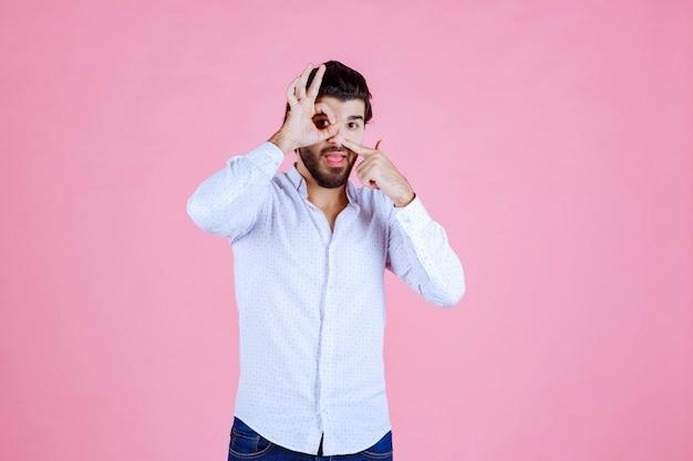 Man in een wit overhemd kijkt over zijn vingers.