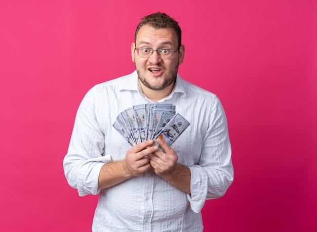Man in een wit overhemd met een bril die een hoop dollargeld vasthoudt en er verbaasd en verrast uitziet terwijl hij over een roze muur staat