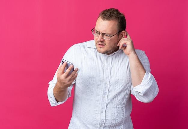 Man in een wit overhemd met een bril die een smartphone vasthoudt die er verward en angstig naar kijkt en over een roze muur staat