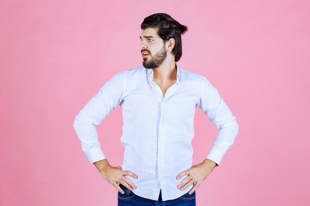 Man in een wit overhemd met neutrale en aantrekkelijke poses.