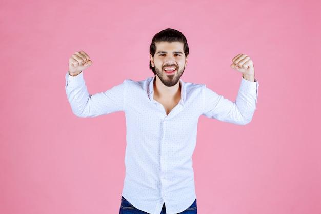 Man in een wit overhemd met zijn spieren en kracht.