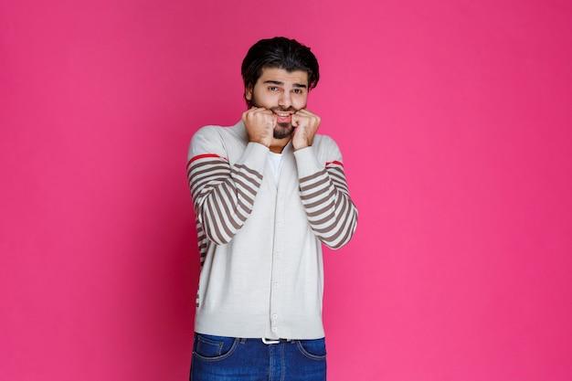 Man in een wit overhemd met zijn vuisten als een doodsbang en bang persoon.