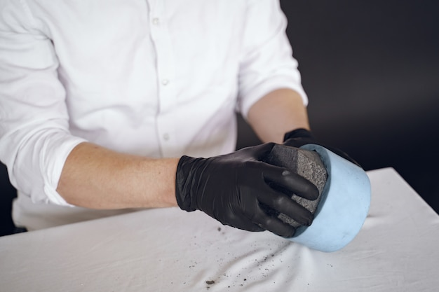 Man in een wit overhemd werkt met een cement