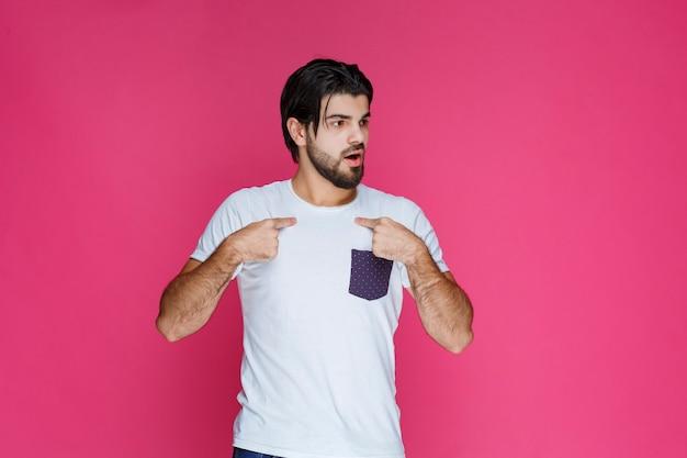 Man in een wit overhemd wijst zichzelf en kijkt verbaasd.