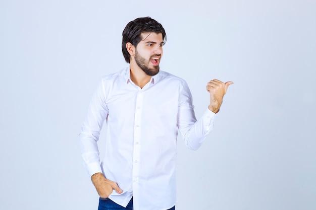 Man in een wit overhemd wijzend naar achteren
