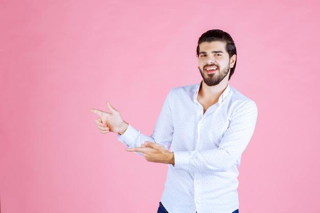 Man in een wit overhemd wijzend naar de linkerkant.