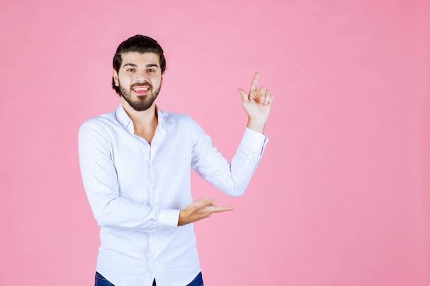 Man in een wit overhemd wijzend naar de rechterkant.