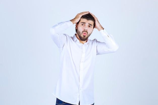 Man in een wit overhemd ziet er verward en verloren uit