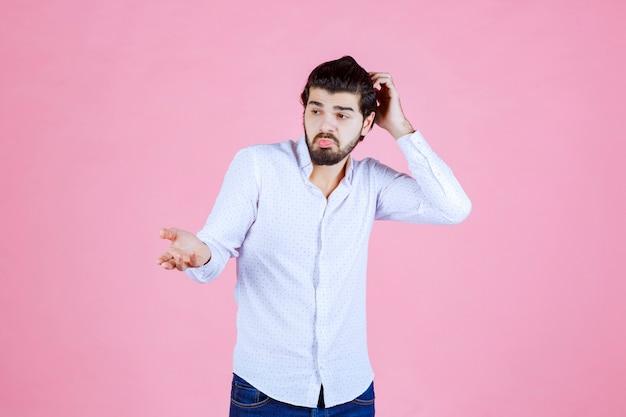 Man in een wit overhemd ziet er verward en verloren uit.