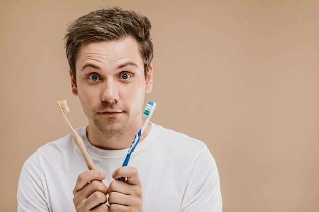 Man in een wit t-shirt die kiest tussen een houten tandenborstel en een plastic tandenborstel