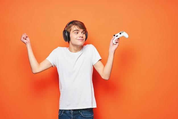 Man in een wit t-shirt met een joystick in zijn handen entertainment games-technologie. hoge kwaliteit foto