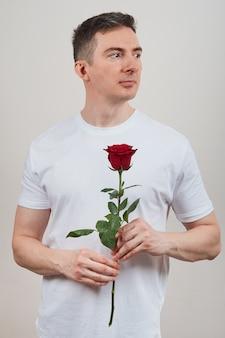 Man in een wit t-shirt met een rode roos in zijn handen