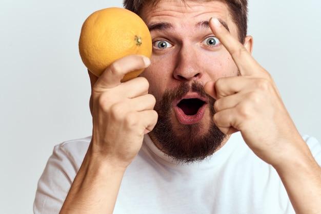Man in een wit t-shirt met gezonde groenten en fruit in zijn handen