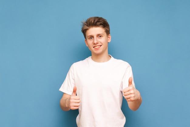 Man in een wit t-shirt staat op een blauw en kijkt naar de camera met een glimlach op zijn gezicht en duimen op