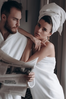 Man in een witte jas en een vrouw in een handdoek