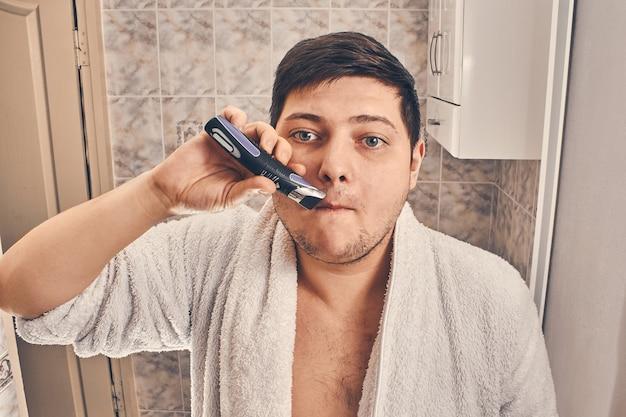 Man in een witte jas scheert zich met een trimmer in de badkamer.