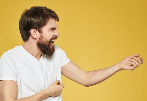 Man in een witte t-shirt handgebaren woede gele achtergrond