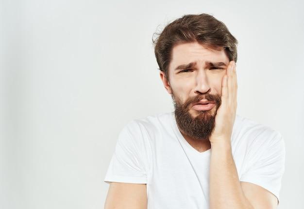 Man in een witte t-shirt handgebaren woede lichte achtergrond