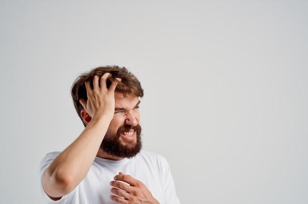 Man in een witte t-shirt hoofdpijn migraine problemen studio behandeling