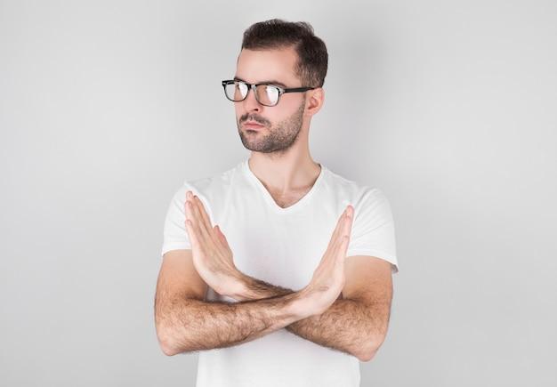 Man in een witte trui vertoont een nee-teken met zijn armen over elkaar.
