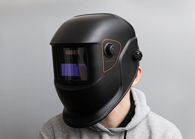 Man in een zwart lasmasker op een lichtgrijze muur, close-up