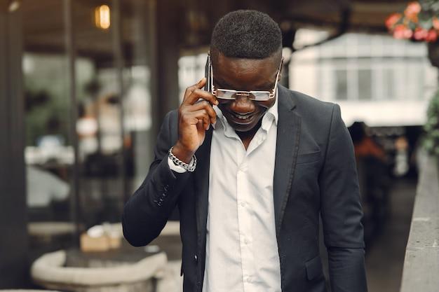 Man in een zwart pak. mannetje met een mobiele telefoon. zakenman op kantoor.