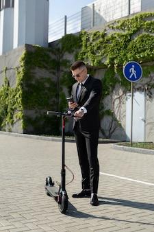 Man in een zwart pak staat naast een elektrische scooter en houdt een telefoon vast