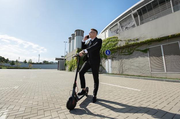 Man in een zwart pak staat naast een elektrische scooter en praat aan de telefoon