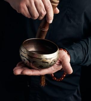 Man in een zwart shirt draait een houten stok rond een koperen tibetaanse kom