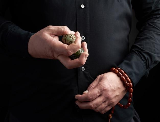 Man in een zwart shirt heeft een groene stenen bal voor religieuze rituelen