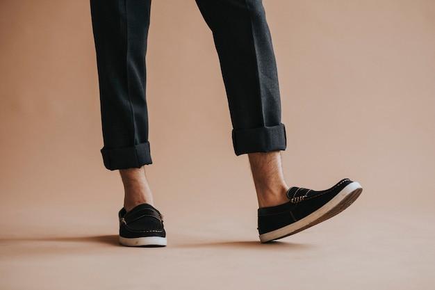 Man in een zwarte broek en slip-on schoenen