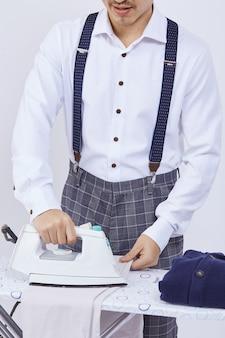 Man in elegante jurk strijken van kleren op wit