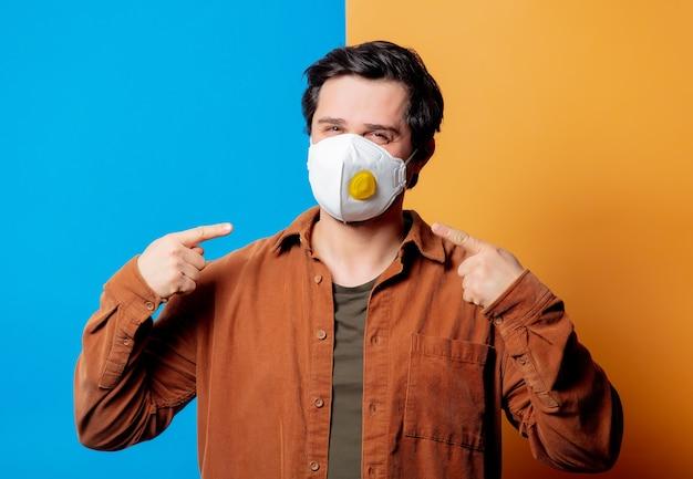 Man in ffp2 gezichtsmasker in een goed humeur op gele en blauwe achtergronden