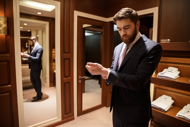 Man in formalwear staande in de garderobe