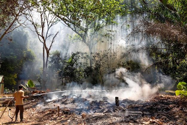 Man in gaasverband en brandslang die vuur probeert te blussen in het bos vuur en rook in de jungle