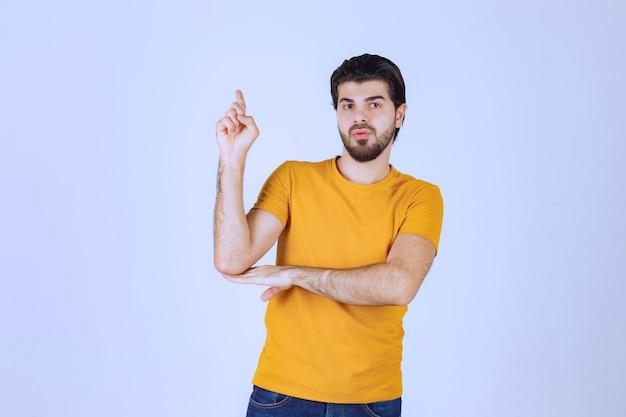 Man in geel overhemd die hierboven iets laat zien.