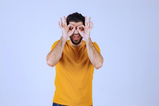 Man in geel overhemd kijkt vooruit