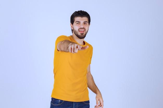 Man in geel overhemd wijst naar iemand vooruit.