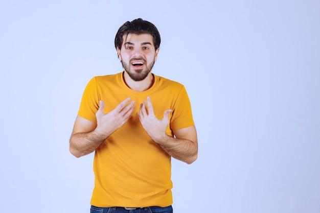 Man in geel overhemd wijzend op zichzelf.
