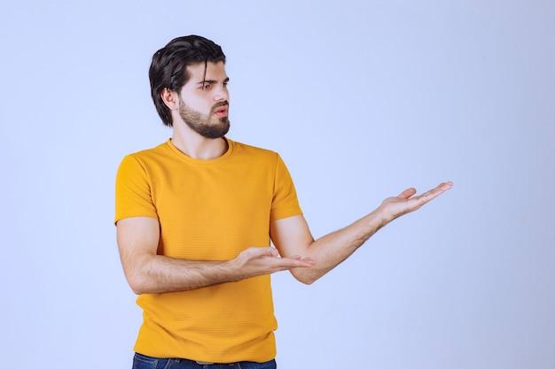 Man in geel shirt met iets in zijn open hand.