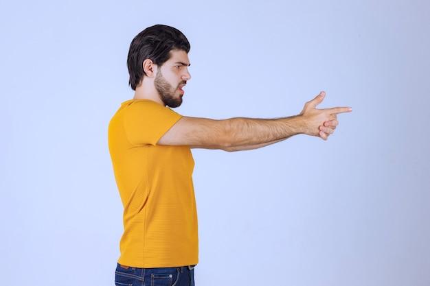 Man in geel shirt met pistoolteken in de hand