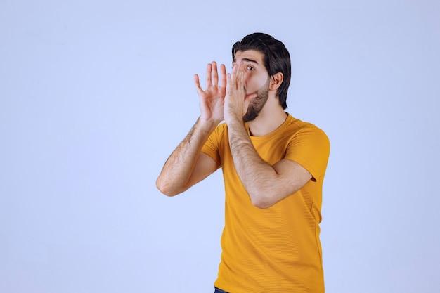 Man in geel shirt schreeuwt het uit