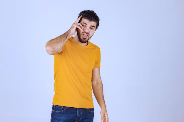 Man in geel shirt staat neutraal zonder reactie