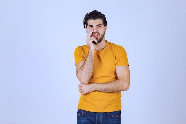 Man in geel shirt ziet er twijfelachtig en denkend uit.